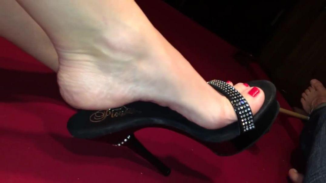 Chica con pies bonitos jugando con los zapatos negros